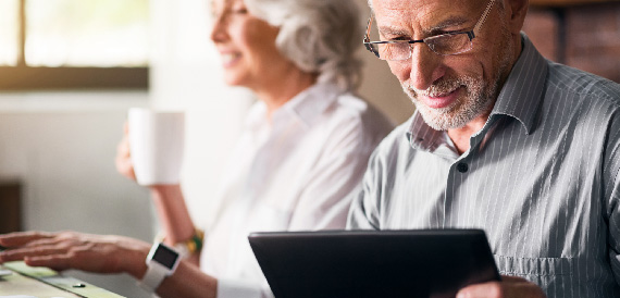 Elderly man checking his account on his tablet.